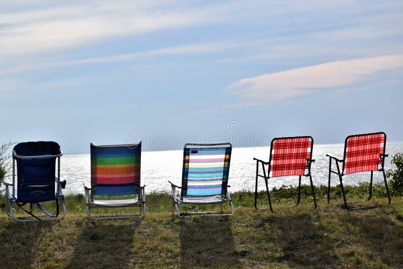 Sedie di spiaggia allineate dal lato della baia fotografie stock libere da diritti