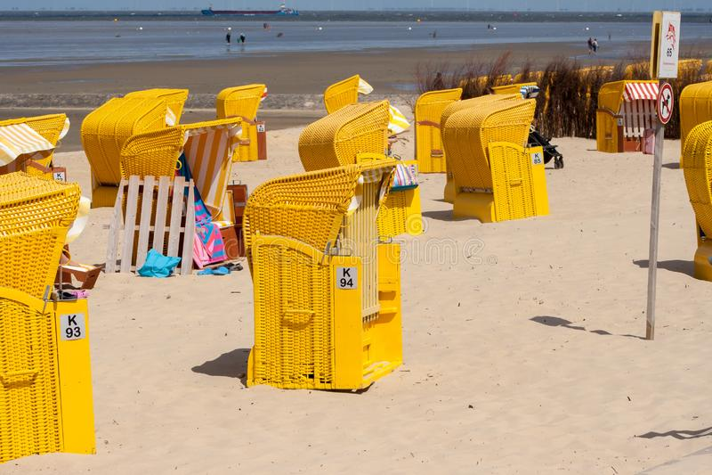 Sedie di spiaggia gialle su una spiaggia sabbiosa fotografia stock libera da diritti