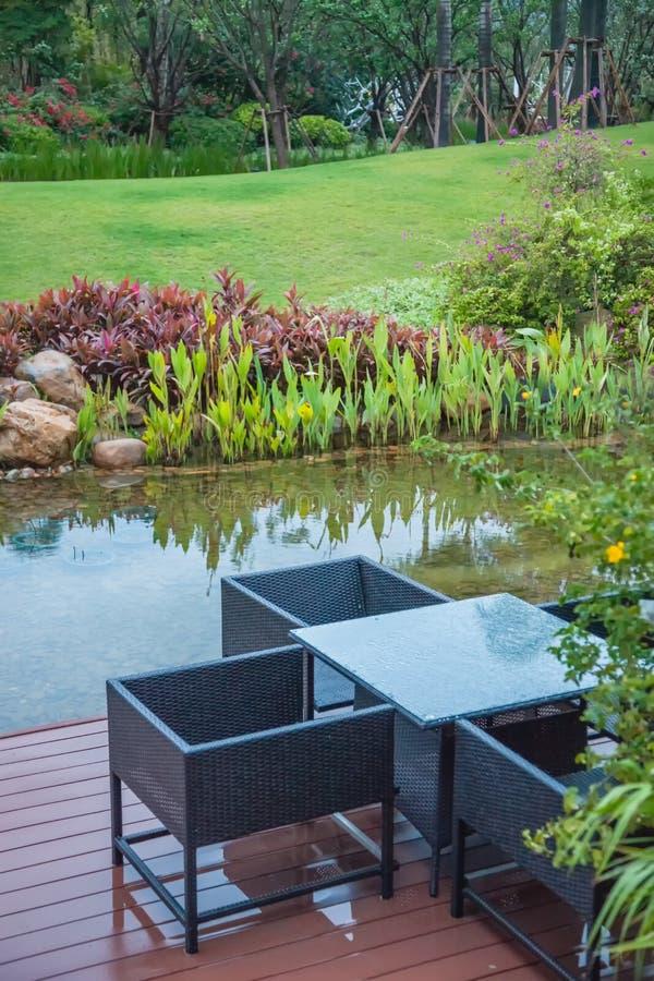Sedie e tavola classiche del rattan sul balcone di legno accanto al piccolo bello lago in un giardino della pianta verde fotografie stock libere da diritti