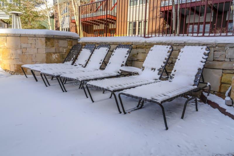 Sedie e tavola di chaise longue all'aperto contro una costruzione un giorno di inverno soleggiato fotografia stock libera da diritti