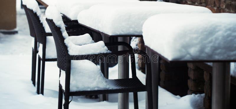Sedie e tavole all'aperto coperte in neve fotografia stock
