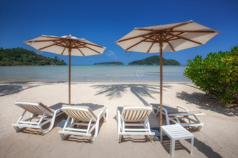 Sedie ed ombrello in spiaggia sabbiosa tropicale fotografia stock libera da diritti