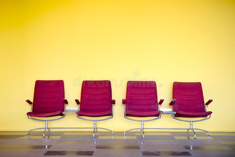Sedie rosse contro la parete gialla fotografia stock