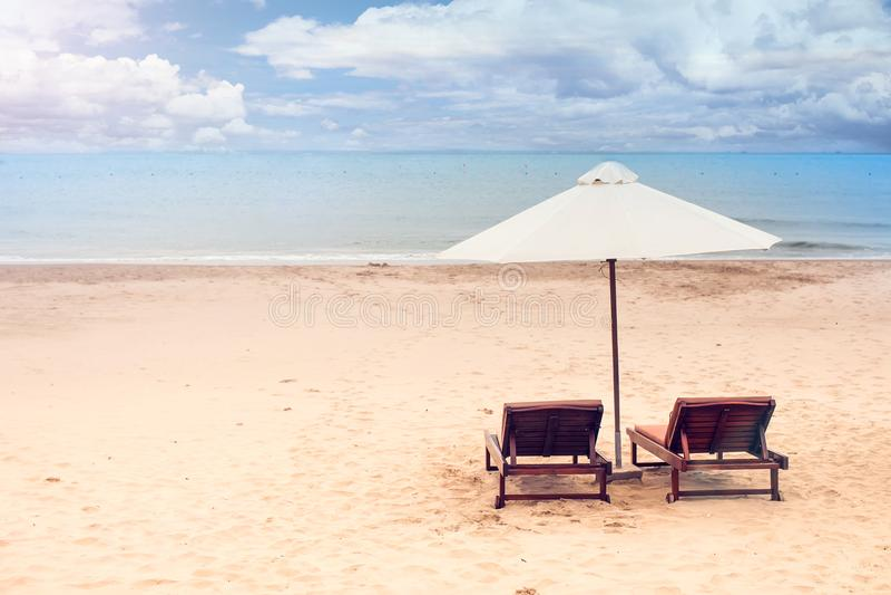 Sedie sulla spiaggia sabbiosa vicino al mare Vacanza estiva e vacat fotografie stock