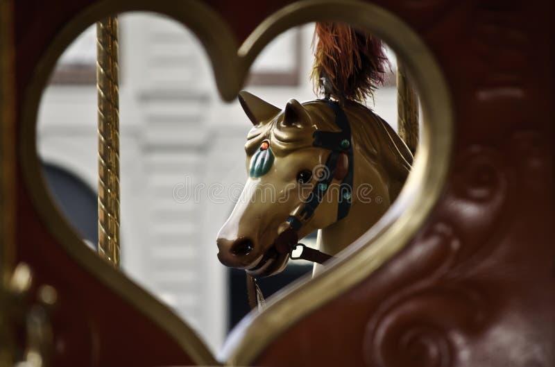 Sedile del carosello con cuore ed il cavallo fotografia stock