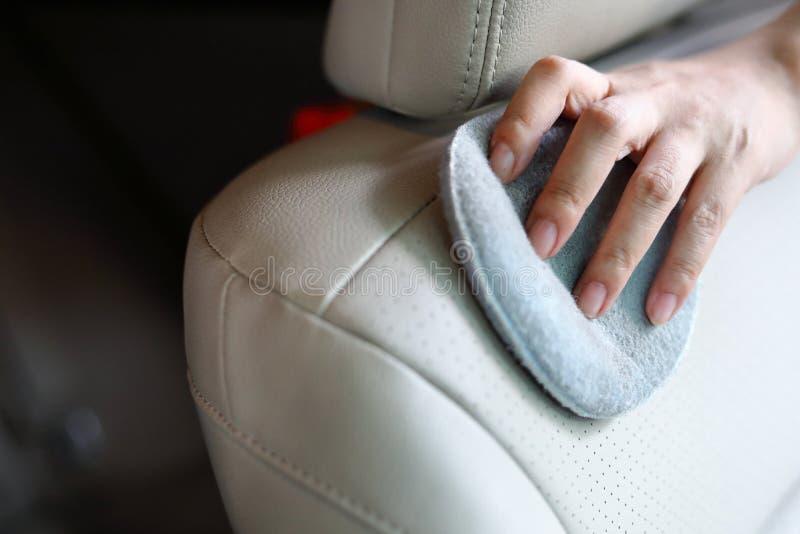 Sedile del cuoio di pulizia della mano della donna in automobile immagine stock