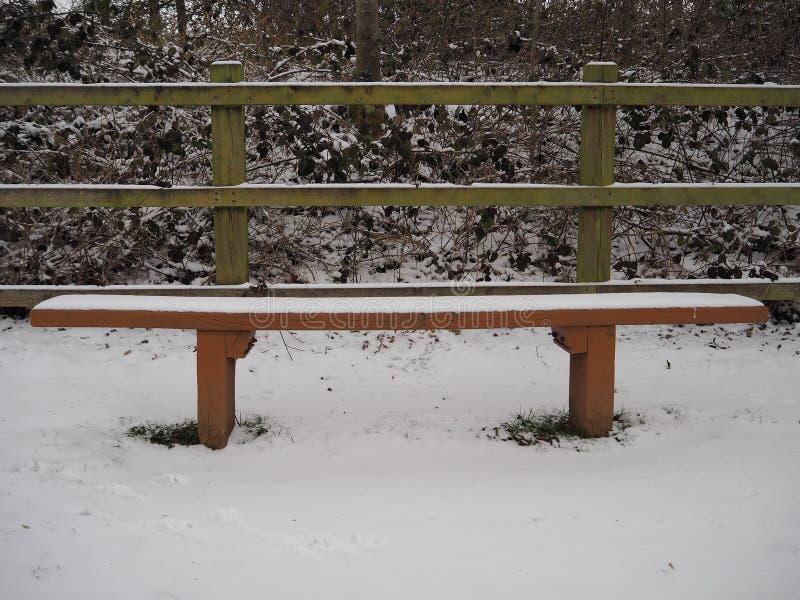 Sedile di banco di legno vuoto coperto perfettamente di neve bianca fotografia stock