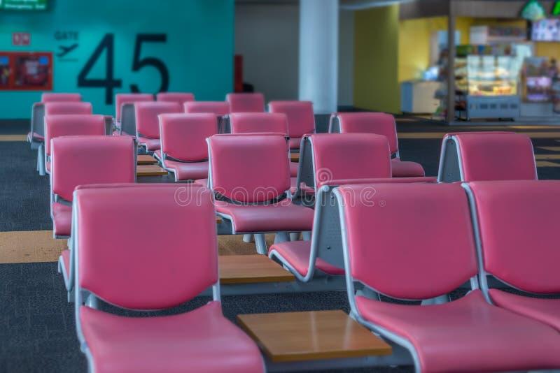 Sedile di cuoio rosso del fuoco selettivo al portone in terminale di aeroporto immagine stock libera da diritti