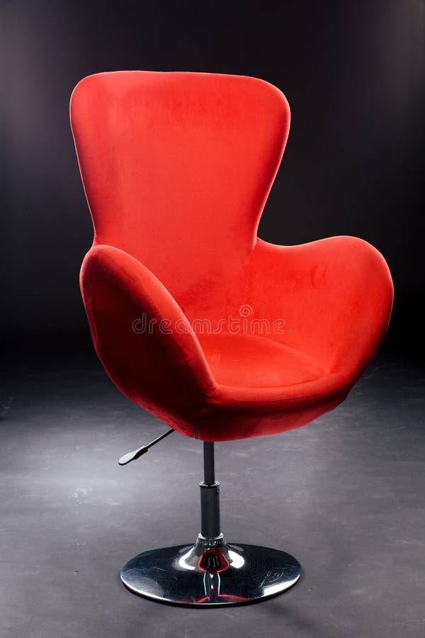 Sedile rosso del velluto sulla gamba d'acciaio nichelata nello studio su un fondo nero Rosso comodo della sedia dell'ufficio fotografie stock libere da diritti