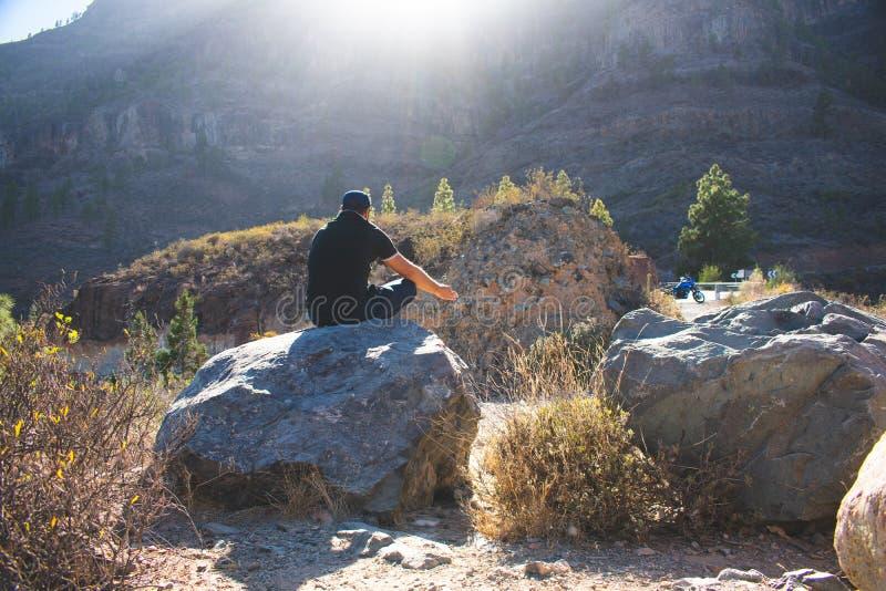 Sedile sulla grande pietra nella montagna, meditazione dell'uomo fotografie stock