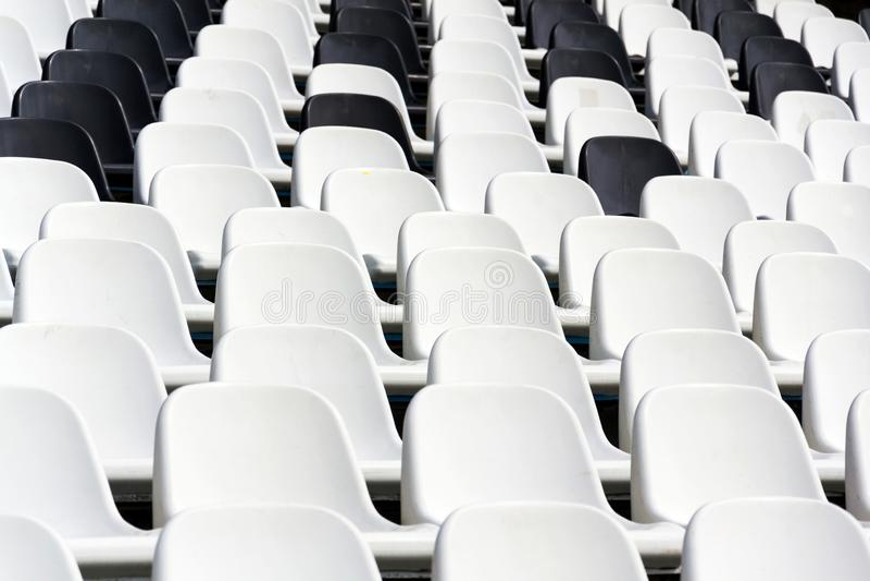 Sedili in bianco e nero vuoti dello stadio misti nelle file, fotografia stock