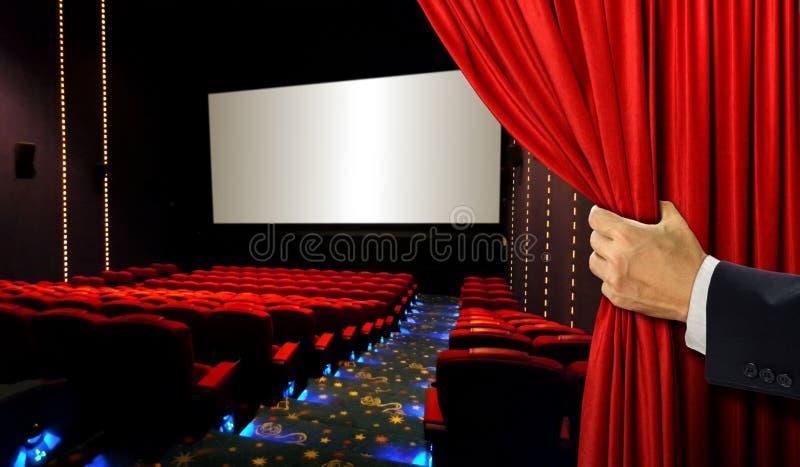 Sedili del cinema e schermo in bianco con la mano che apre tenda rossa fotografia stock