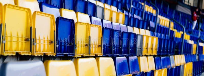 Sedili vuoti di plastica gialli e blu dello stadio immagini stock