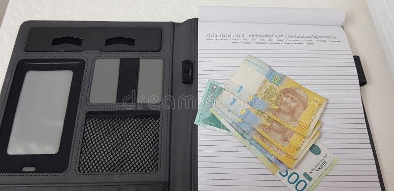 Sedlar av den ukrainska hryvniaen och serbiska dynars lägger på den öppna anteckningsboken royaltyfri foto