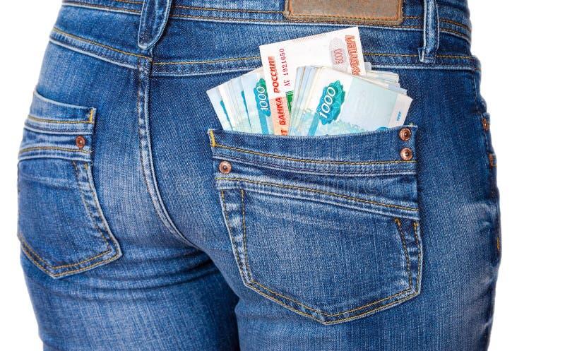 Sedlar för den ryska rublet som klibbar ut ur den tillbaka jeansen, stoppa i fickan arkivfoton