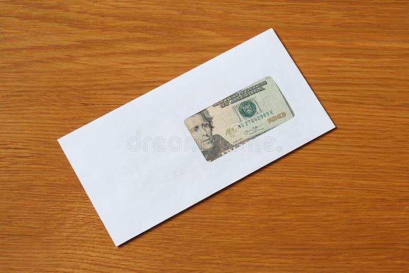 Sedlar för några US dollar i det vita svarta kuvertet för en muta i kontoret på tabellen arkivfoto