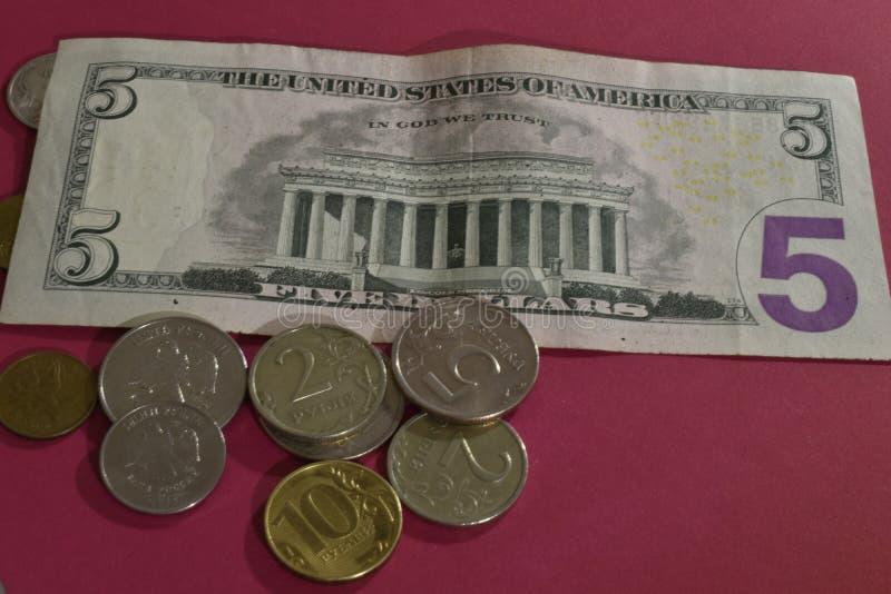 Sedlar och mynt p? r?d bakgrund royaltyfri fotografi