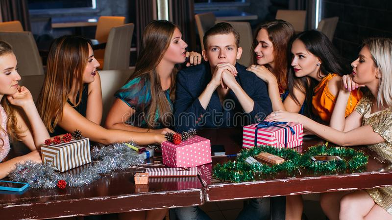Seduction at Christmas party. Playful mood. Females flirting with handsome man, young people company in club, New Year decoration, seductive concept stock photography