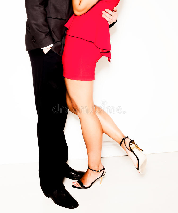 Seduction in the office. As a businessman in a suit stands holding a women in a red dress and high heels in an intimate embrace, lower bodies isolated on white royalty free stock photos