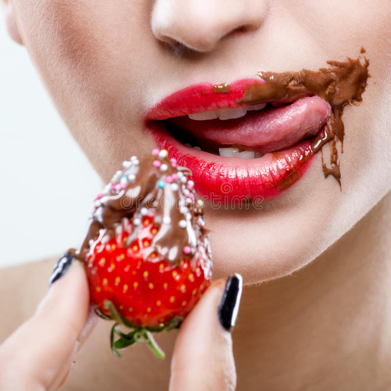 Seduction - red female lips with chocolate mouth , holding strawberries.  royalty free stock image