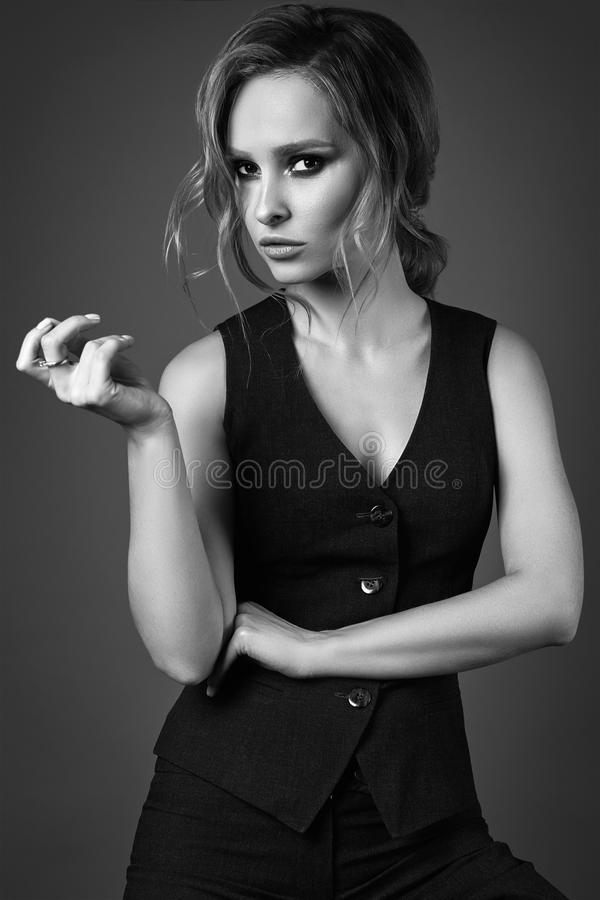 Seductive blonde girl in pants and a man`s waistcoat stock photo