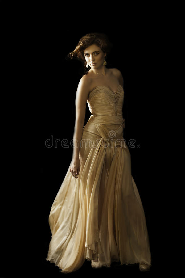 Seductive brunette woman in couture evening dress. Portrait of a sensual young woman with auburn hair, wearing gold earrings, bronzed goddess makeup and a pale stock photo