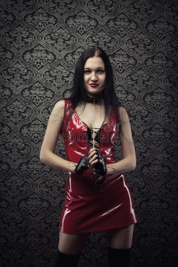 Seductive doll. Attractive girl in red latex dress over vintage background stock photography