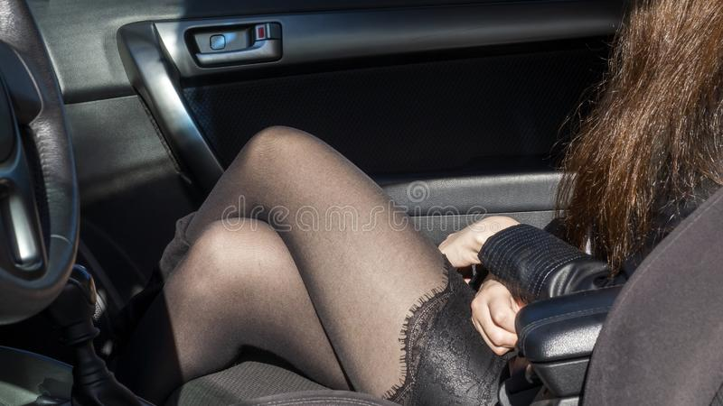 Seductive female legs in black pantyhose and short skirt in car stock photography
