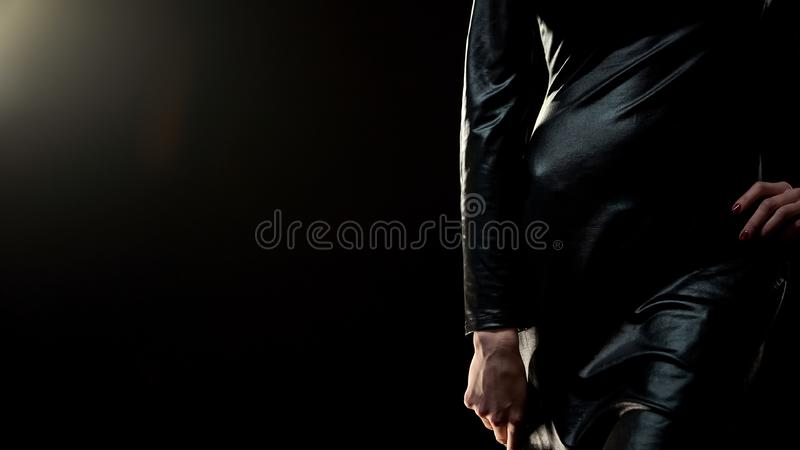 Seductive fit lady in little black dress standing against black background royalty free stock images