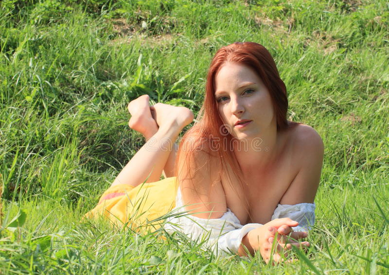 Seductive girl. Young seductive woman - brunette barefoot girl in white blouse and yellow skirt lying on green grass stock image