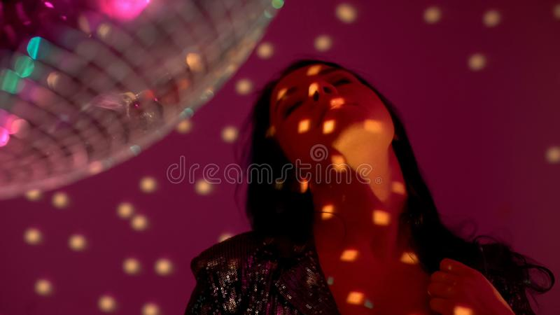 Seductive lonely woman dancing at party by disco ball, searching for boyfriend. Stock photo stock photo
