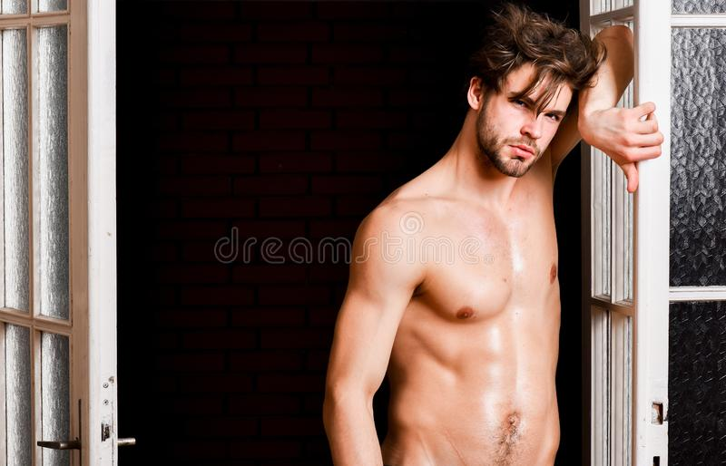 Seductive lover full of desire. Man confident lover near door. attractive macho tousled hair coming out through. Bedroom door. bachelor lover concept. Guy royalty free stock photo