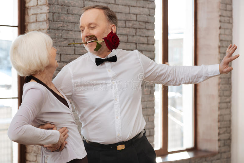 Seductive man tangoing with senior woman in the dance studio stock images