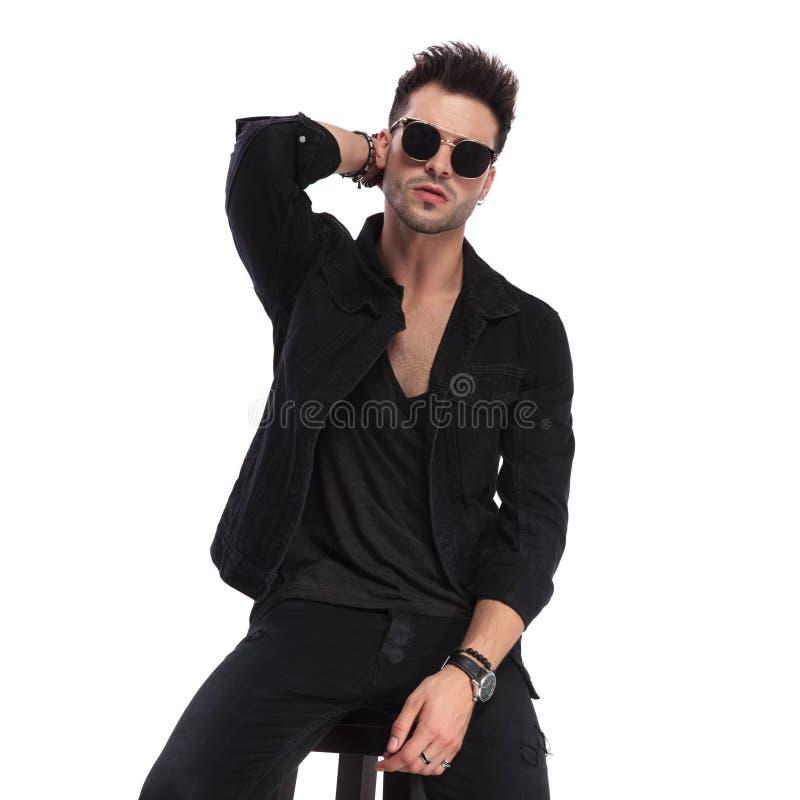 Seductive seated man wearing sunglasses arranging his hair. Portrait of seductive seated man wearing sunglasses arranging his hair on white background royalty free stock photos