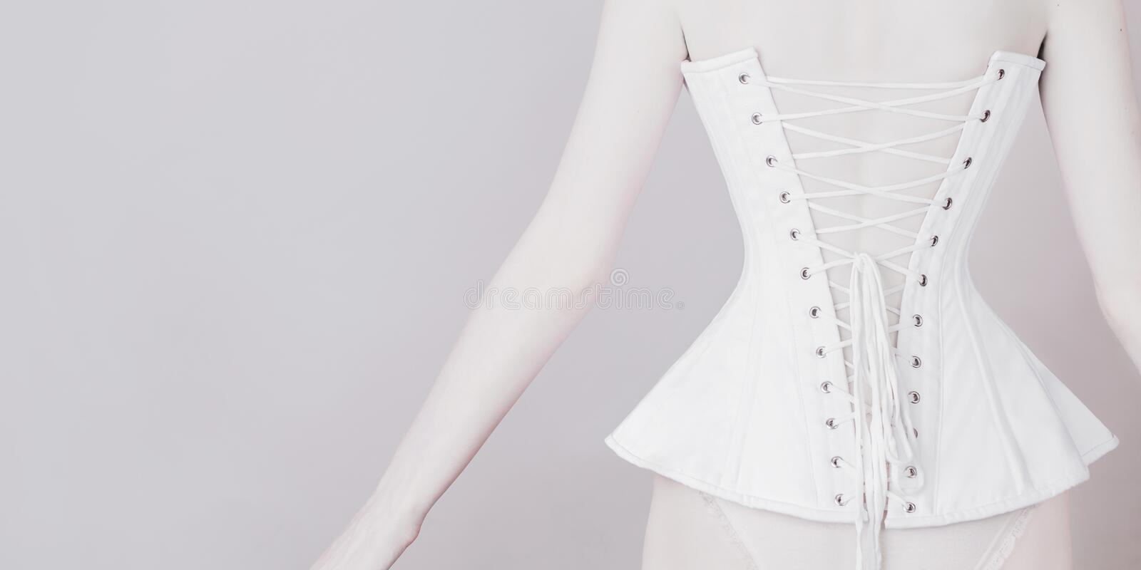 Seductive outfit. Slender girl in waist pulling corset on light background. Sexual bdsm lingerie. Lady in narrow laced corset stock photo