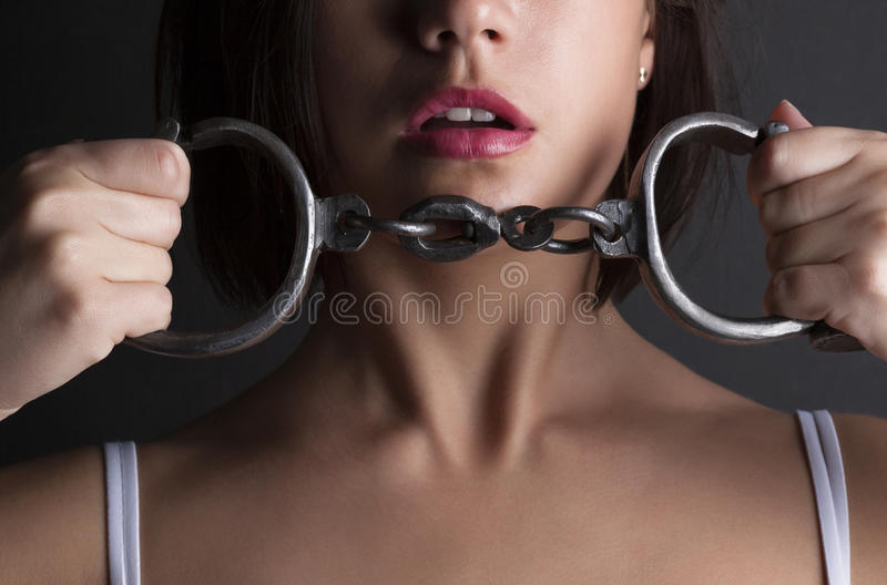 Seductive woman with handcuffs. A seductive woman with handcuffs stock photos