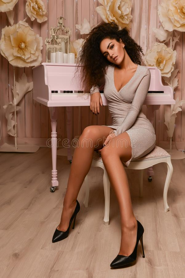 Seductive woman sitting. Gorgeous woman in short beige dress and black high heels, long legs, curly volume hair, sitting near piano stock photography