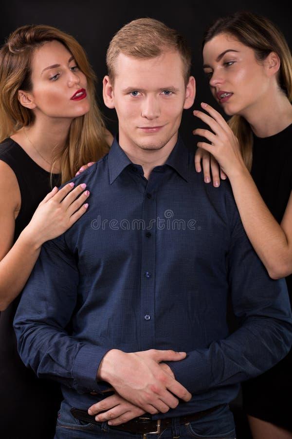 Seductive women tempting handsome man. Love triangle - seductive women tempting handsome man stock images