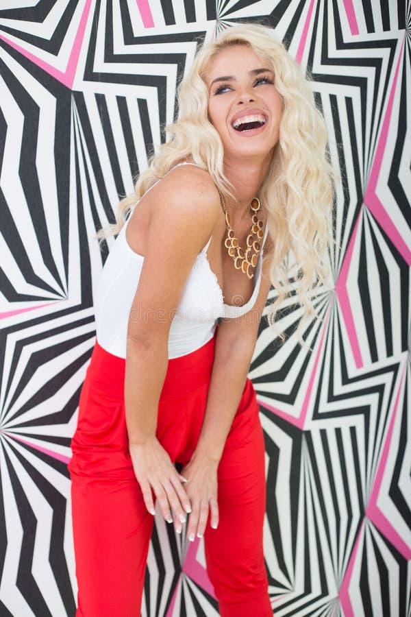 Seductive Young Blond Woman Posing at Printed Wall royalty free stock images