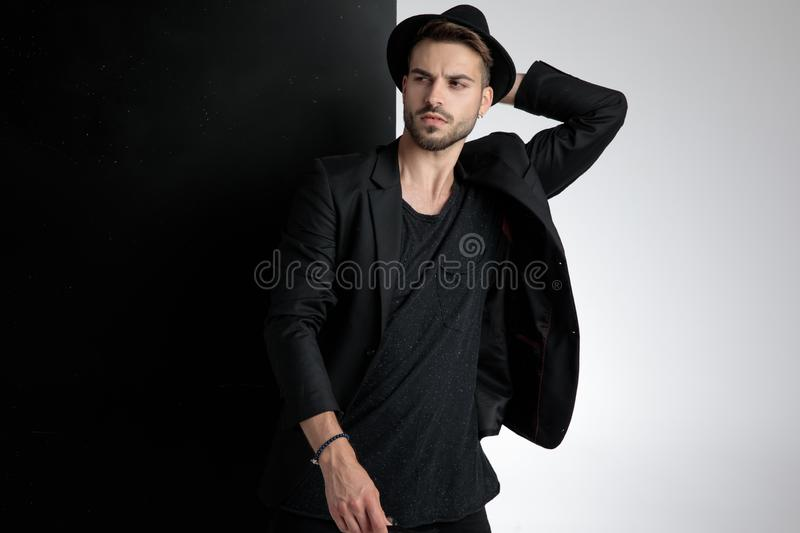 Seductive young man holding hand to head in studio royalty free stock images
