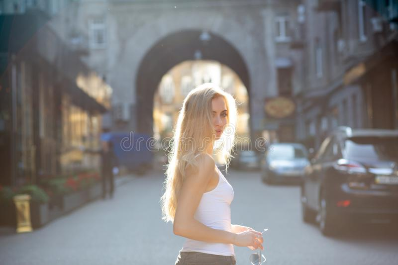 Seductive young model with long hair holding glasses, posing at the passage in rays of sun. Copy space stock image