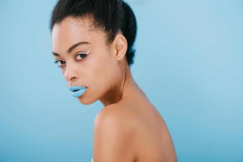 seductive young woman with creative makeup and blue lips looking at camera royalty free stock photography
