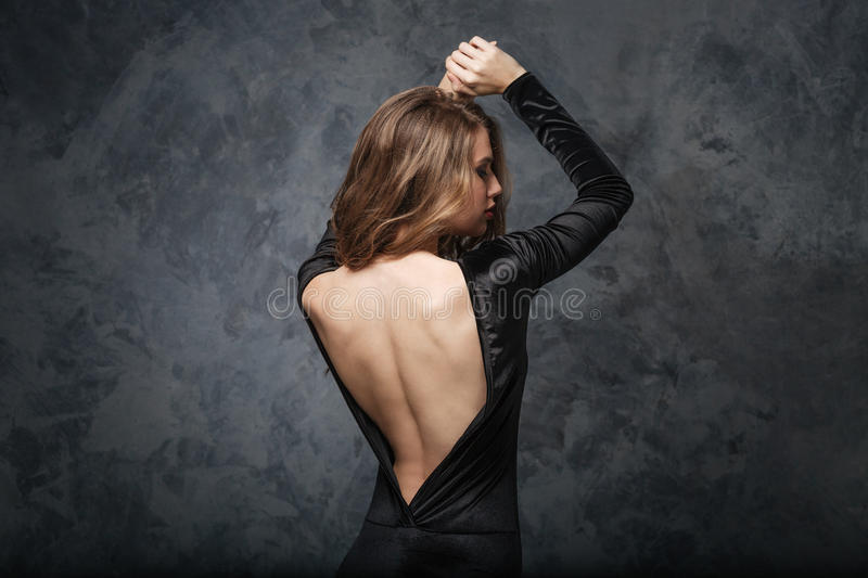 Seductive young woman in evening dress with open back. Back view of seductive young woman in evening dress with open back posing with raised hands over grey stock photography