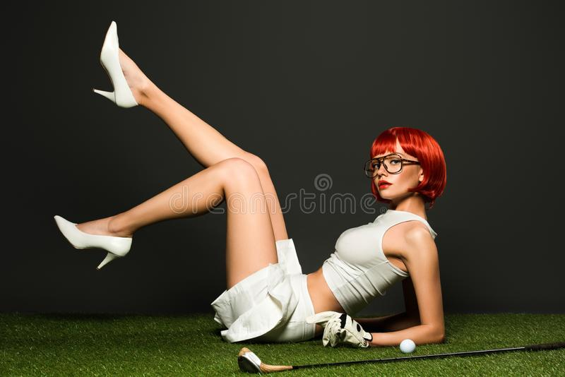 seductive young woman in high heels and skirt lying on green grass with golf equipment stock image
