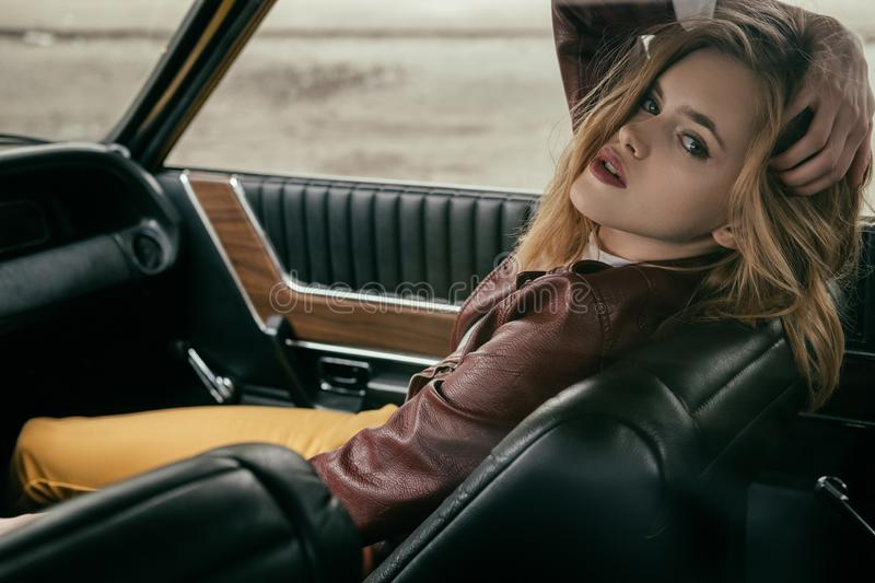 seductive young woman in leather jacket looking at camera while sitting in car stock photos