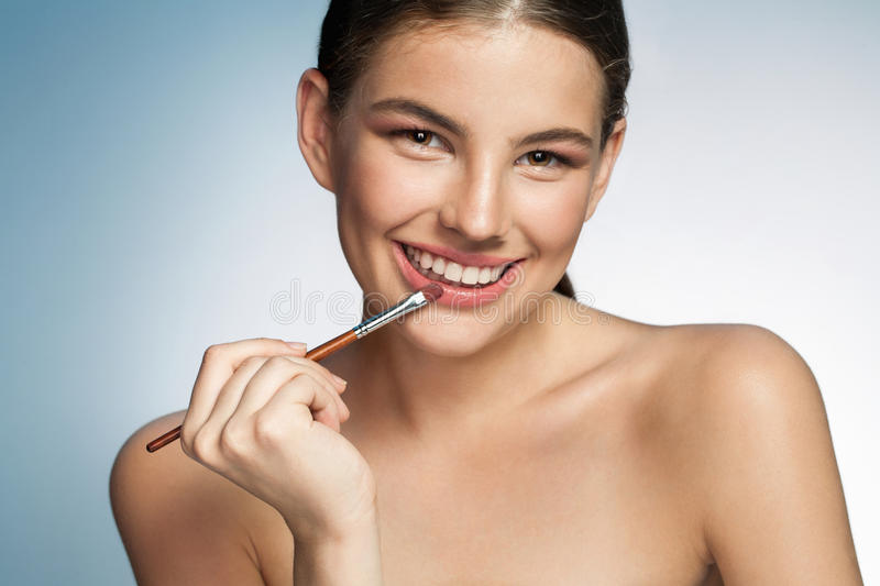 Seductive young woman with lip brush royalty free stock image