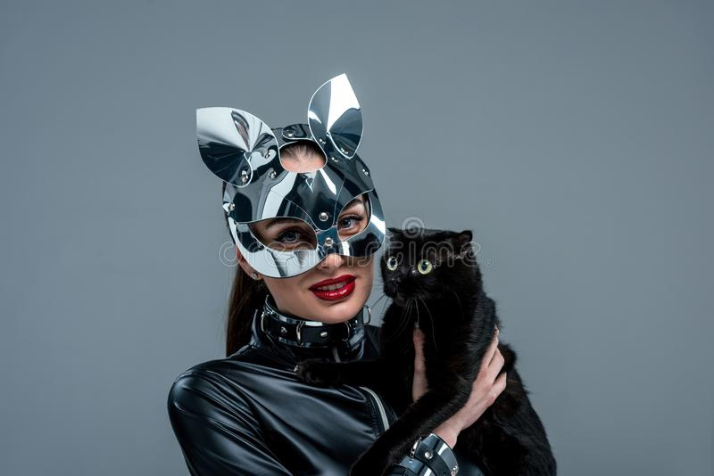 Seductive young woman in mask holding black cat stock image