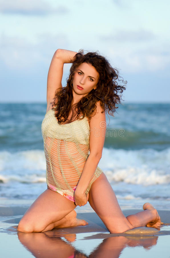 Seductive young woman. Sitting on the beach royalty free stock photos