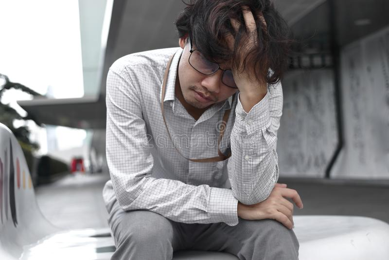 Seduta asiatica stanca e annoiata e sensibilità dell'uomo di affari frustrate fotografia stock libera da diritti