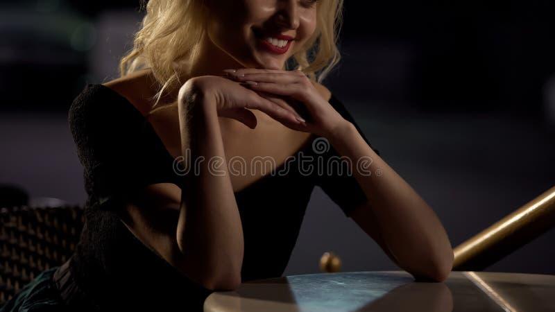 Seduta bionda sorridente graziosa in caffè che ascolta il ragazzo, data romantica immagini stock libere da diritti
